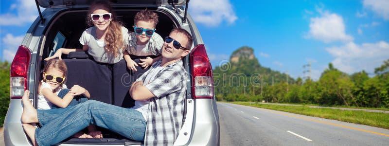Lycklig fader och barn som sitter i bilen på den soliga dagen arkivfoton