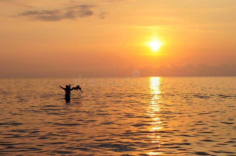 Lycklig fader- och barnsimning i havet på den härliga färgrika solnedgången royaltyfria bilder