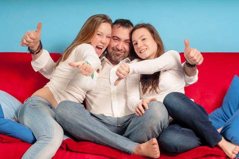 Lycklig fader och döttrar på soffan royaltyfri foto