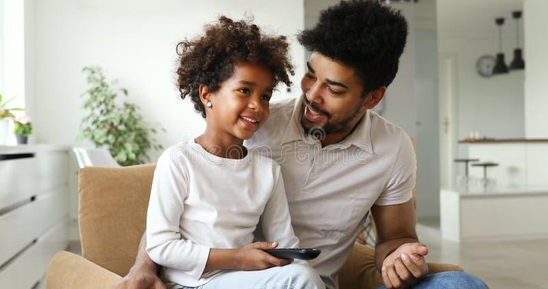 Lycklig fader- och dotter- och hålla ögonen påtv hemma arkivbilder