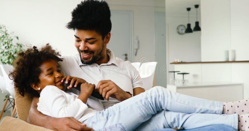 Lycklig fader- och dotter- och hålla ögonen påtv hemma arkivfoton