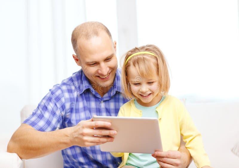 Lycklig fader och dotter med minnestavlaPCdatoren arkivfoto