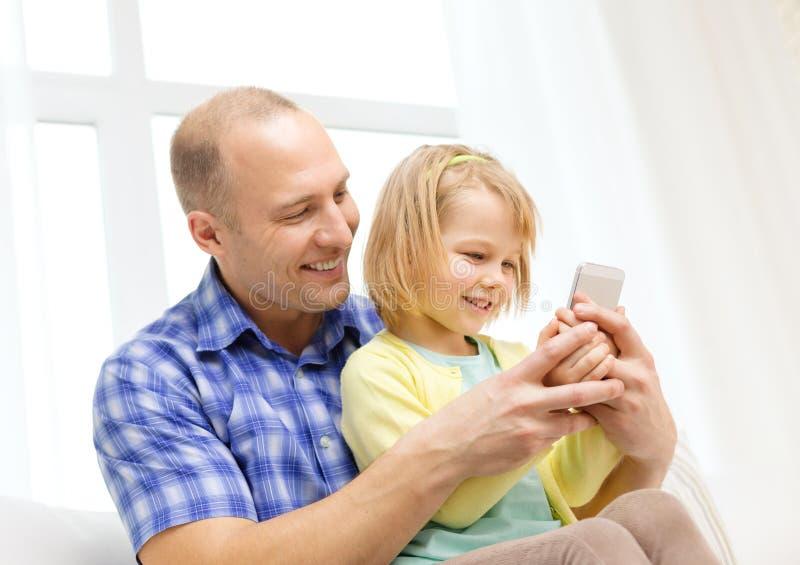 Lycklig fader och dotter med smartphonen royaltyfri bild