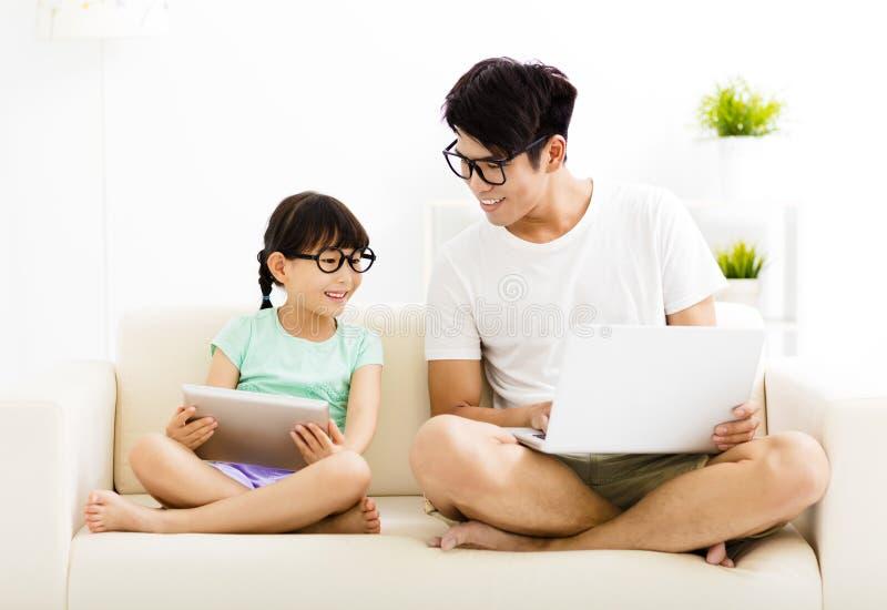 Lycklig fader och dotter som använder bärbara datorn fotografering för bildbyråer