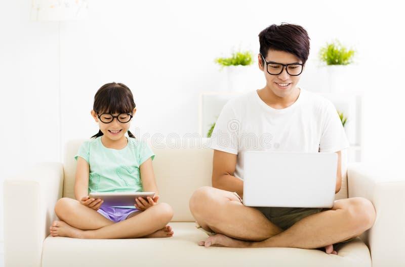 Lycklig fader och dotter som använder bärbara datorn arkivbilder