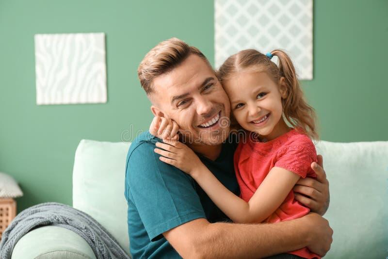 Lycklig fader och dotter som hemma kramar arkivbild