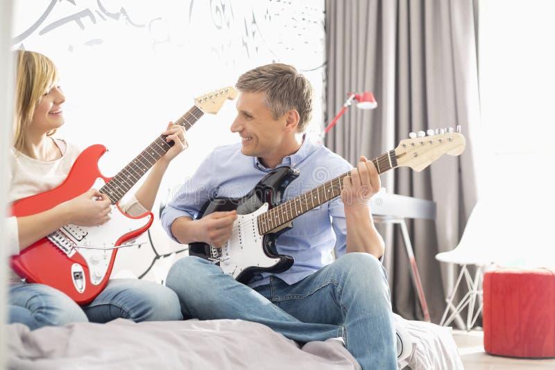 Lycklig fader och dotter som hemma spelar gitarrer royaltyfri fotografi