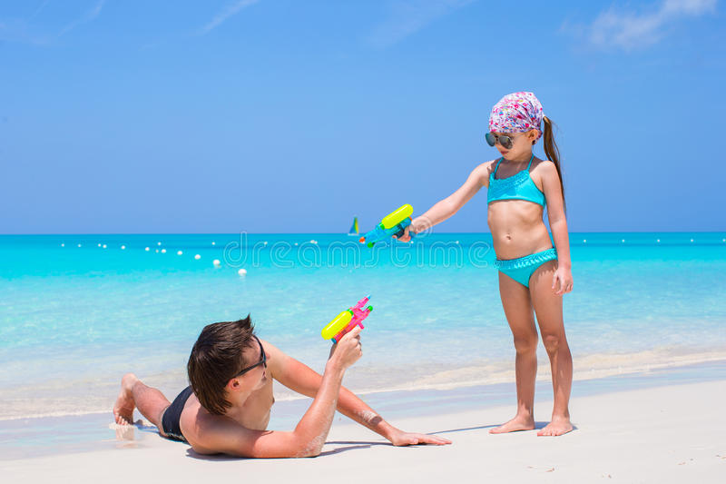 Lycklig fader och hans förtjusande lilla dotter på den tropiska stranden som har gyckel fotografering för bildbyråer