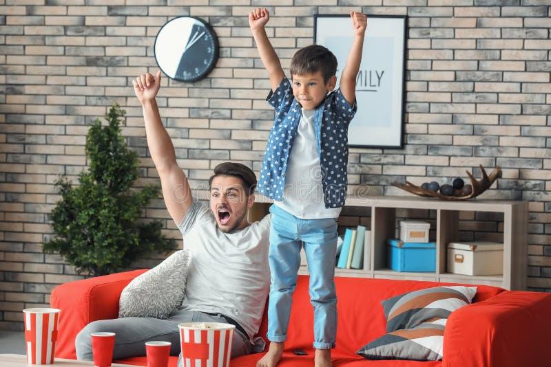 Lycklig fader och hans hållande ögonen på TV för son på soffan hemma arkivbilder