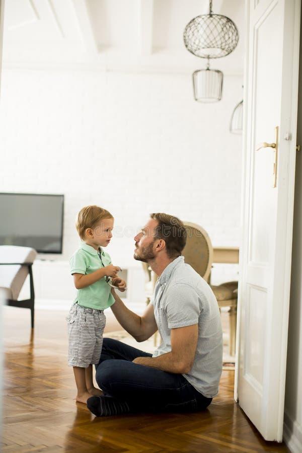 Lycklig fader och liten son som hemma spelar och har gyckel arkivfoton