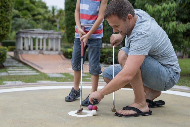 Lycklig fader och liten son som spelar mini- golf fotografering för bildbyråer