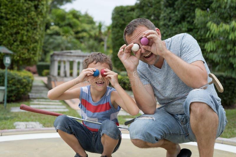 Lycklig fader och liten son som spelar mini- golf royaltyfri fotografi