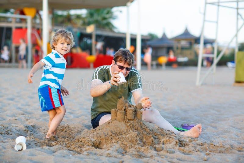 Lycklig fader och och liten sonbyggnadssandslott på sandbea fotografering för bildbyråer