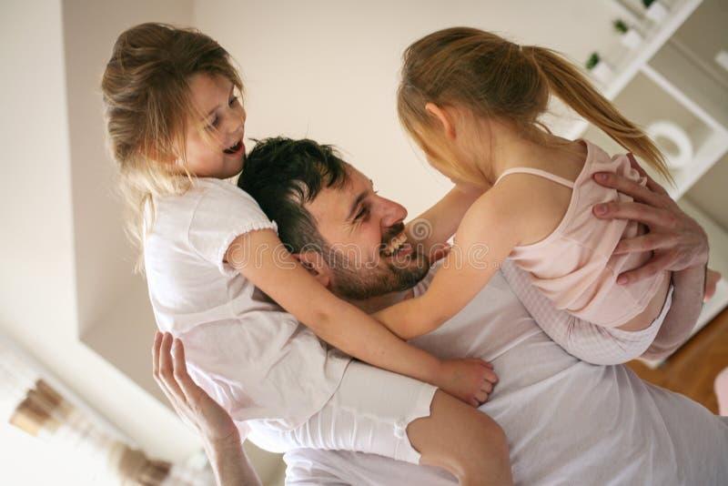 Lycklig fader och små döttrar som hemma spenderar tid royaltyfri fotografi