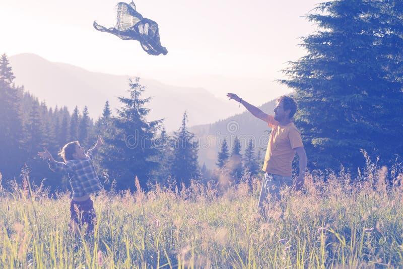 Lycklig fader och son som har gyckel på den alpina ängen fotografering för bildbyråer