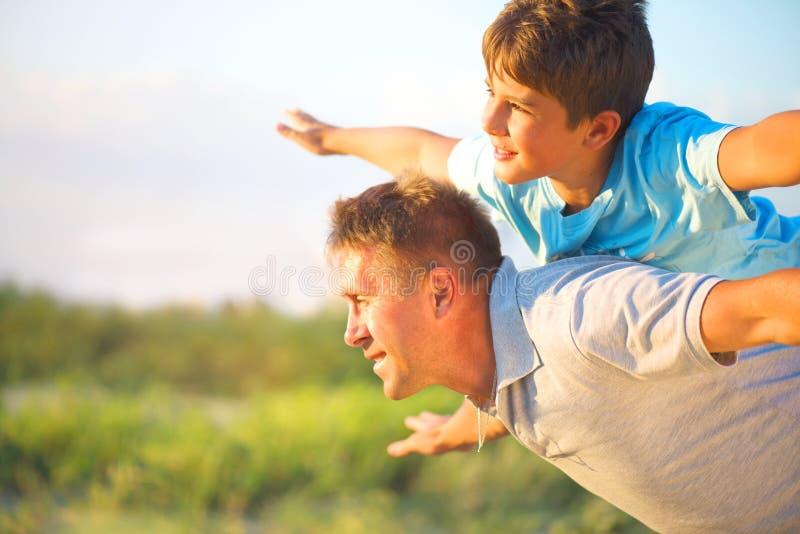 Lycklig fader och son som har roligt utomhus fotografering för bildbyråer