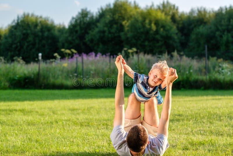 Lycklig fader och son som har roligt utomhus- på äng royaltyfri foto