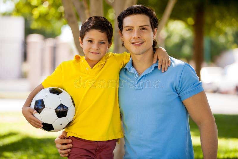 Lycklig fader och son som spelar fotboll royaltyfri fotografi