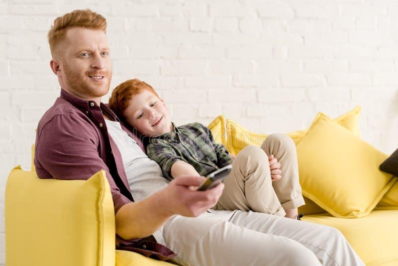 lycklig fader och son som tillsammans sitter på soffan och använder den avlägsna kontrollanten, medan hålla ögonen på tv royaltyfri fotografi