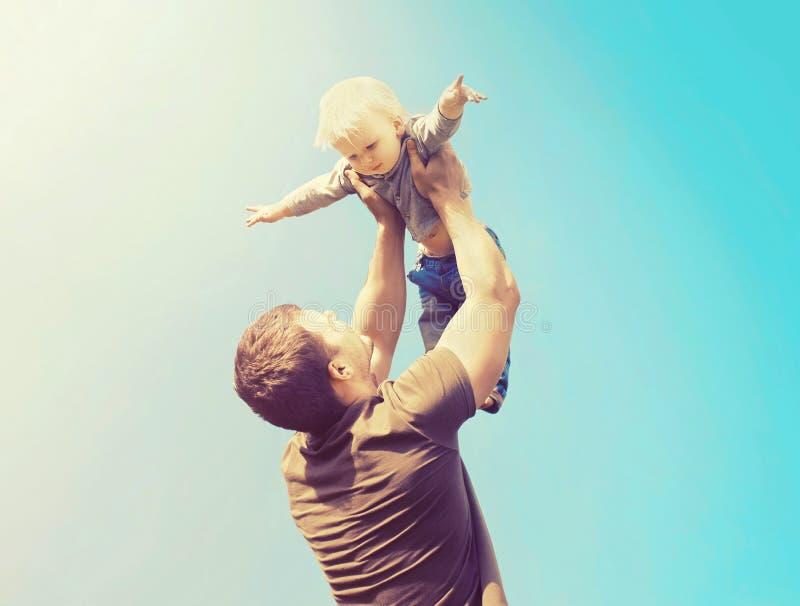 Lycklig fader och son som tillsammans spelar ha gyckel utomhus över himmel royaltyfria foton