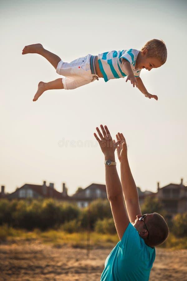 Lycklig fader och son som tillsammans spelar på stranden Fader som kastar hans son i luften arkivbild