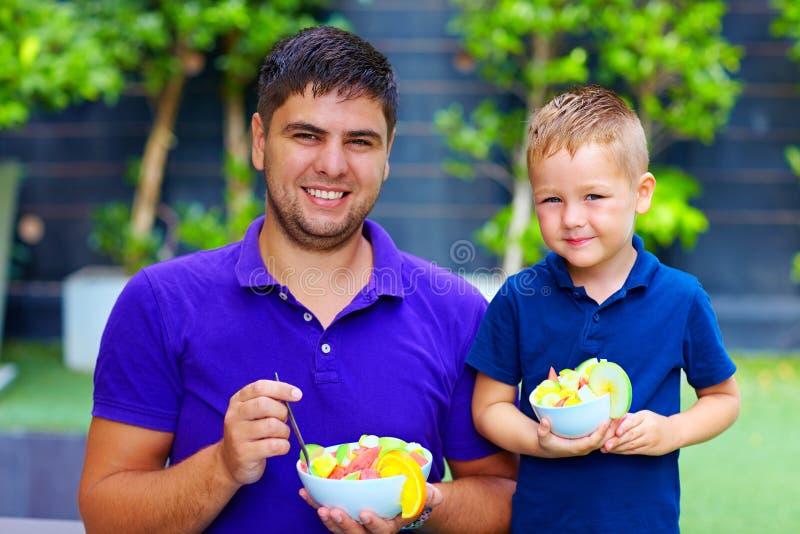 Lycklig fader och son som tycker om sallad för ny frukt royaltyfri fotografi