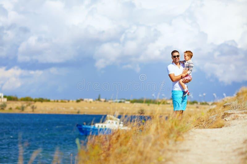 Lycklig fader och son som tycker om sjösidalandskap fotografering för bildbyråer