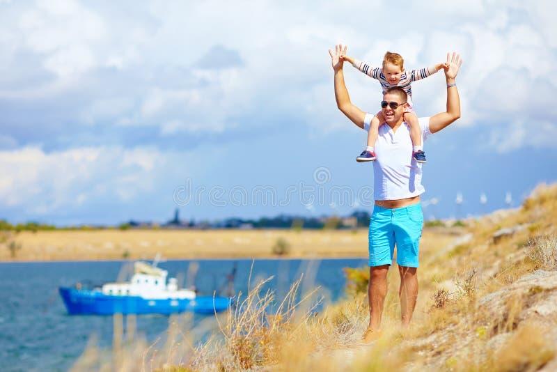 Lycklig fader och son som tycker om sjösidalandskap royaltyfri fotografi