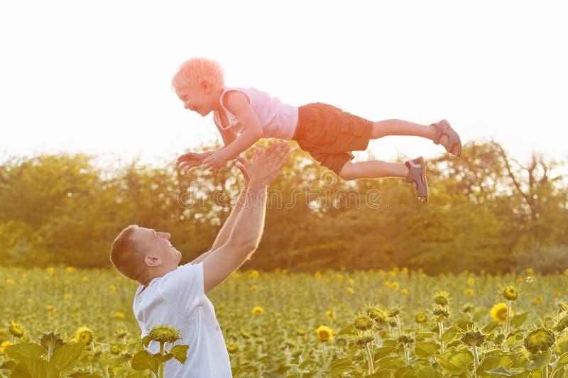 Lycklig fader som kastar upp lite att skratta sonen p? ett gr?nt f?lt av solrosor N?rbild royaltyfri fotografi