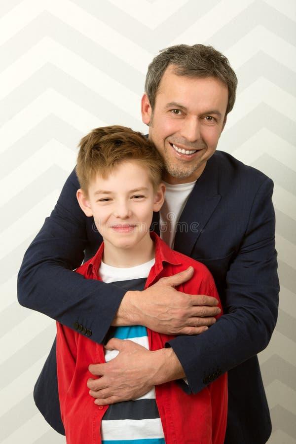 Lycklig fader som omfamnar sonen arkivbild