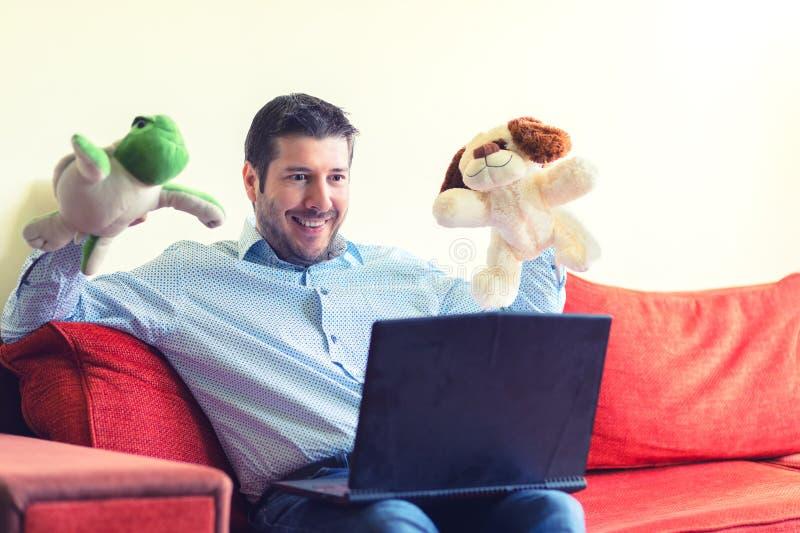 Lycklig fader som sitter på appell för ho för soffa meddelande video på bärbara datorn med hans barn som visar dem leksaker och g arkivbild