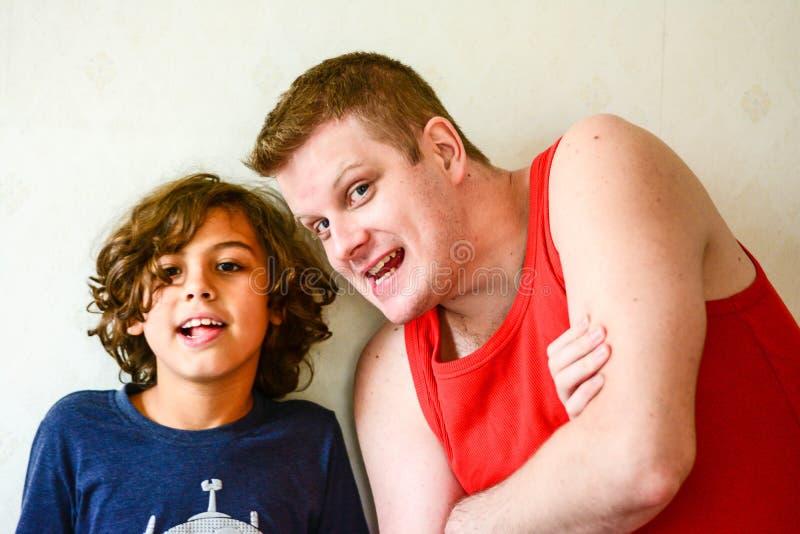Lycklig fader som spelar med pojken i kök fotografering för bildbyråer