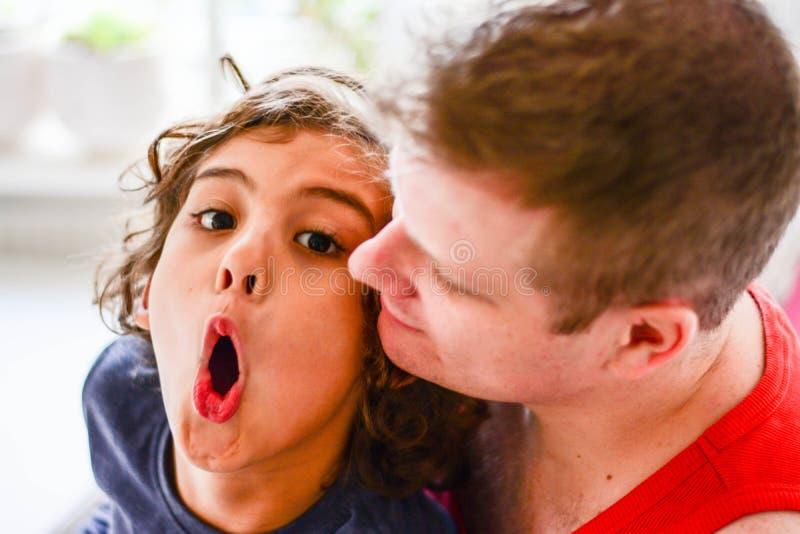 Lycklig fader som spelar med pojken i kök arkivfoton