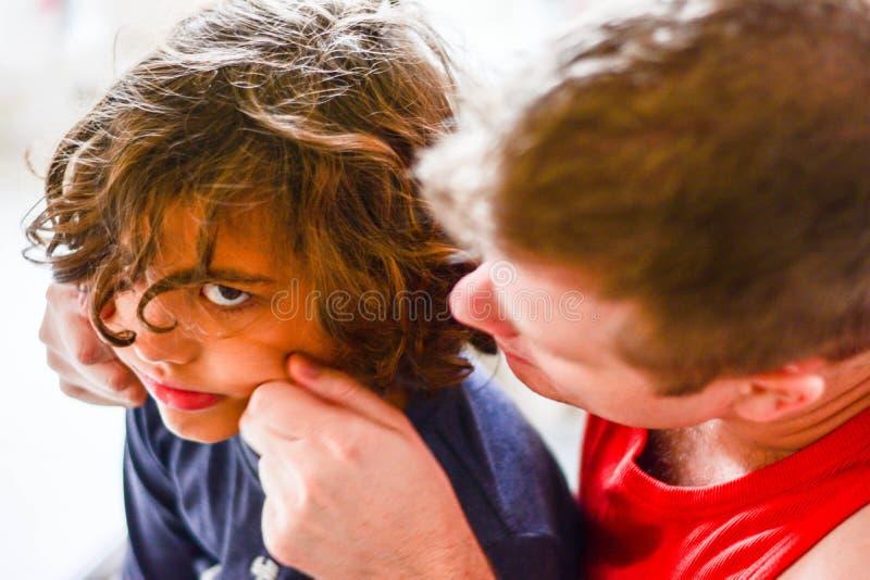 Lycklig fader som spelar med pojken i kök royaltyfria foton