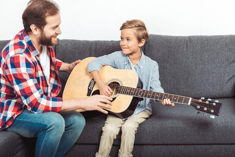 lycklig fader som undervisar den gulliga lilla sonen som spelar gitarren fotografering för bildbyråer