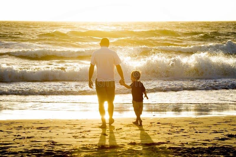 Lycklig faderinnehavhand av den lilla sonen som tillsammans går på stranden med barfota arkivfoto
