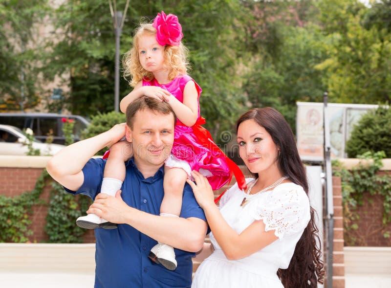 Lycklig familj av fadern, den gravida modern och barnet i utomhus- på en sommardag Ståendeföräldrar och unge på naturen Positiv m royaltyfri fotografi