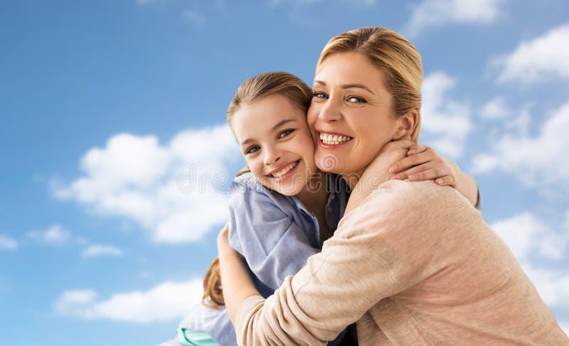 Lycklig familj av flickan och modern som kramar över himmel arkivbilder