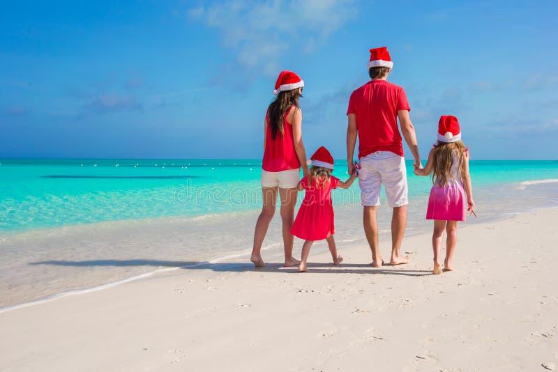 Lycklig familj av fyra i julhattar på vit arkivfoton