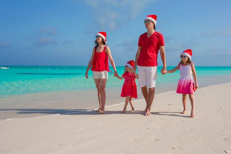 Lycklig familj av fyra i julhattar under arkivbild