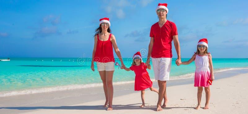 Lycklig familj av fyra i julhattar under royaltyfri bild