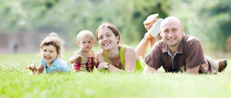 Lycklig familj av fyra  i sommar parkera royaltyfri foto