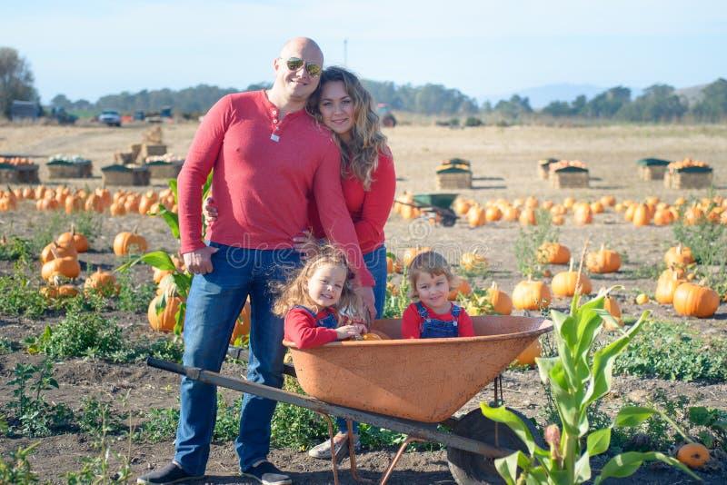 Lycklig familj av fyra på lantgårdfältet royaltyfri fotografi