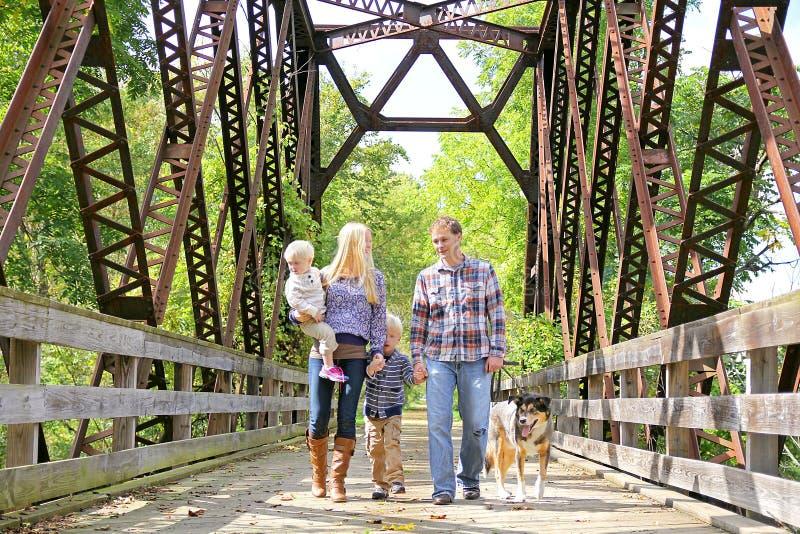 Lycklig familj av fyra personer som går hunden utanför på bron arkivbild