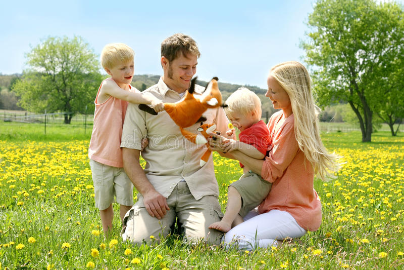 Lycklig familj av fyra personer som spelar med leksaker utanför i blomma arkivbilder
