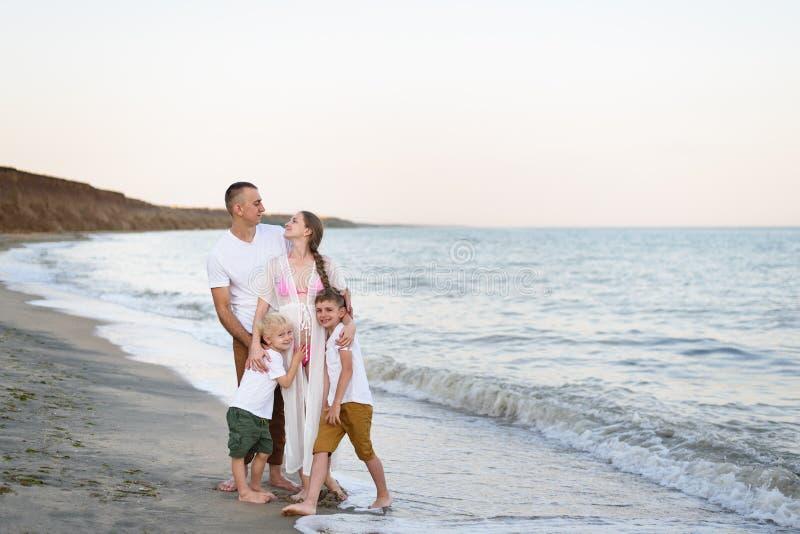 Lycklig familj av fyra som kramar på föräldrarna för havskust, den gravida modern och två söner royaltyfria bilder