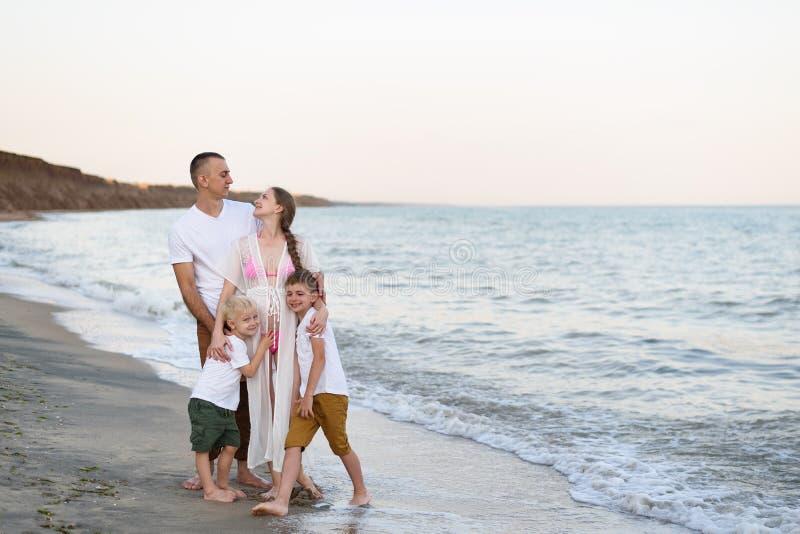 Lycklig familj av fyra som kramar på föräldrarna för havskust, den gravida modern och två söner royaltyfri fotografi
