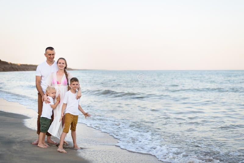 Lycklig familj av fyra som kramar på föräldrarna för havskust, den gravida modern och två söner arkivbild