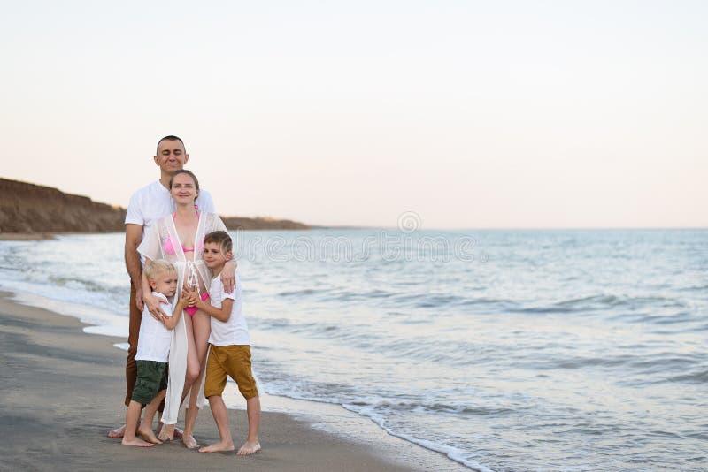 Lycklig familj av fyra som kramar på föräldrarna för havskust, den gravida modern och två söner royaltyfri foto