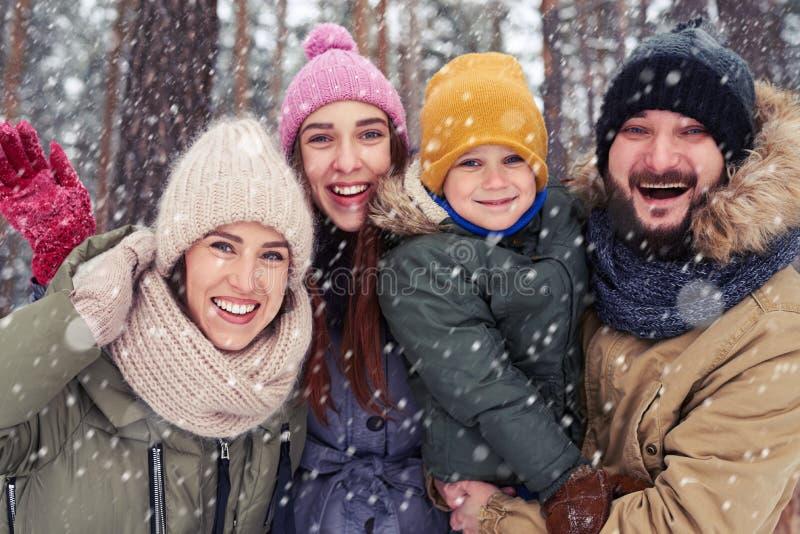 Lycklig familj av fyra som står i den snöig skogen i vinter fotografering för bildbyråer